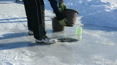 Man draw water frozen ice hole pour bucket winter skate site Stock Footage