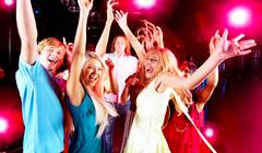 Joyful teens having fun in night club while dancing Stock Photos