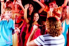 photo of happy teenage friends looking at guy singing in mic at party - stock photo
