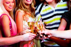 portrait of boozing young people toasting at party - stock photo