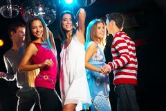 Joyful girls dancing in night club with their friends near by Stock Photos