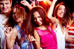Portrait of glad teens looking at camera with smiles during disco Stock Photos