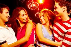 portrait of laughing couples looking at each other at party - stock photo
