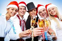 portrait of smart colleagues with flutes of champagne wishing you merry christma - stock photo