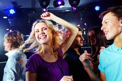 Image of pretty blonde dancing on background of clubbing friends Stock Photos