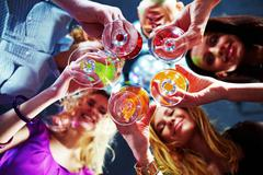 Bottom view of many friends holding glasses with cocktails Stock Photos