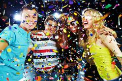 Photo of excited teenagers embracing at party under falling confetti Stock Photos