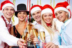 portrait of smart colleagues with flutes of champagne celebrating christmas - stock photo