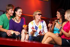 Image of happy teenagers holding the cocktails and chatting Stock Photos