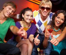 Portrait of young people with flutes showing thumbs up in the nightclub Stock Photos