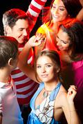 gorgeous woman in smart dress dancing in crowd of clubbers - stock photo
