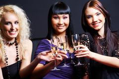 Portrait of three fashionable young women with flutes looking at camera Stock Photos