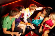 Stock Photo of portrait of friends with cocktails sitting on the sofa in the nightclub and chat