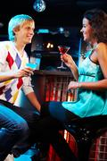 Portrait of attractive couple looking at each other and chatting in the bar Stock Photos