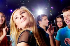 Image of pretty girl looking upwards on background of clubbing friends Stock Photos