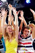 photo of excited teenagers raising their arms in joy - stock photo
