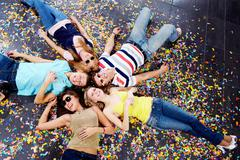 Below angle of group of happy friends looking at camera Stock Photos