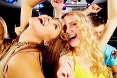 two joyful girls laughing in night club at disco - stock photo