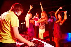 Smart deejay spinning turntables with dancing teens on background Stock Photos