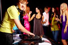 smart deejay working at disco with dancing teens on background - stock photo