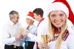 Stock Photo of portrait of beautiful female with champagne on background of her partners