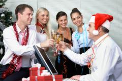 image of cheering associates making toast with ceo in santa cap at corporate par - stock photo
