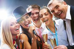 Photo of businesspeople with flutes of sparkling champagne singing christmas son Stock Photos