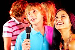 photo of handsome guy singing at party with happy girlfriend near by - stock photo