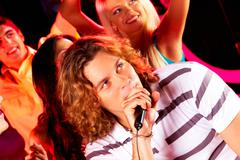 photo of happy guy singing at party with company of friends dancing behind - stock photo