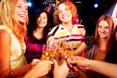 portrait of group of happy young people toasting at party - stock photo