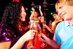 Portrait of happy couple toasting at party on background of joyful friends havin Stock Photos