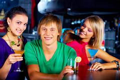 Portrait of two girls with martini glasses surrounding happy guy in the nightclu Stock Photos