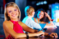 Stock Photo of image of pretty girl looking at camera with her friends behind in the nightclub