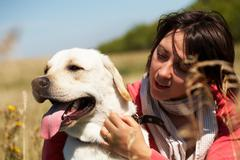 close-up of dog with tongue hanging out and woman embracing its - stock photo