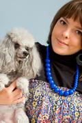 photo of grey poodle with its master in studio - stock photo