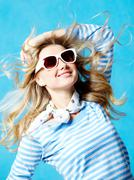 portrait of beautiful teenager in modern clothes and sun glasses on a blue backg - stock photo