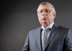 photo of senior employer looking at camera on black background - stock photo