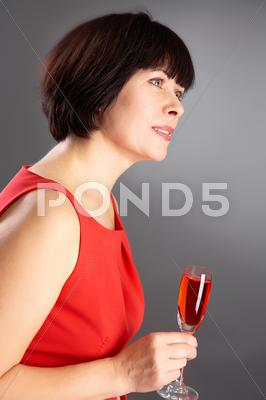 Stock photo of portrait of middle aged female with flute of red wine