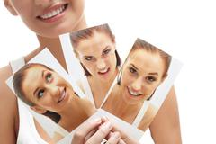Close-up of young female holding three images of herself Stock Photos