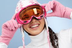 happy woman in goggles and knitted winter cap - stock photo