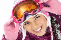 Pretty woman in goggles and winter clothes looking at camera with smile Stock Photos