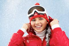 pretty woman in goggles and winter sportswear looking at camera with smile - stock photo