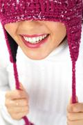 Vertical image of playful woman in knitted winter cap smiling Stock Photos