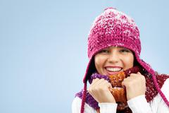 photo of pretty woman in knitted winter cap and scarf looking at camera with smi - stock photo
