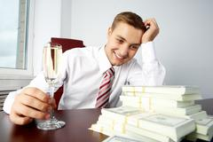 Image of young successful employer looking at heap of dollar bills and touching Stock Photos