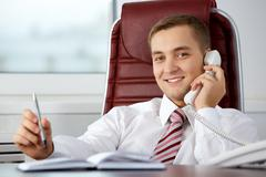 photo of smart businessman calling somebody and smiling during communication - stock photo