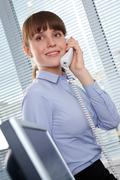 photo of smart businesswoman calling somebody in office - stock photo
