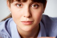 face of pretty girl with serene expression looking at camera - stock photo