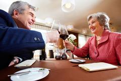 Image of senior couple celebrating at elegant restaurant Stock Photos
