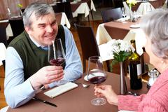 Image of couple with wine glasses sitting at a restaurant Stock Photos
